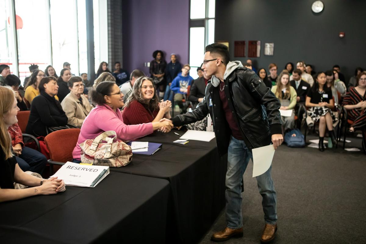 Young person shakes hand with judges in a crowded room