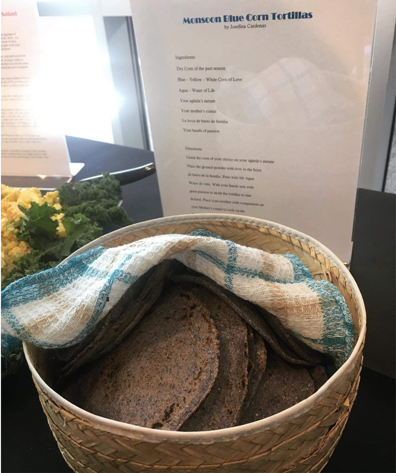 A basket with blue corn tortillas partially covered with a colorful cloth.