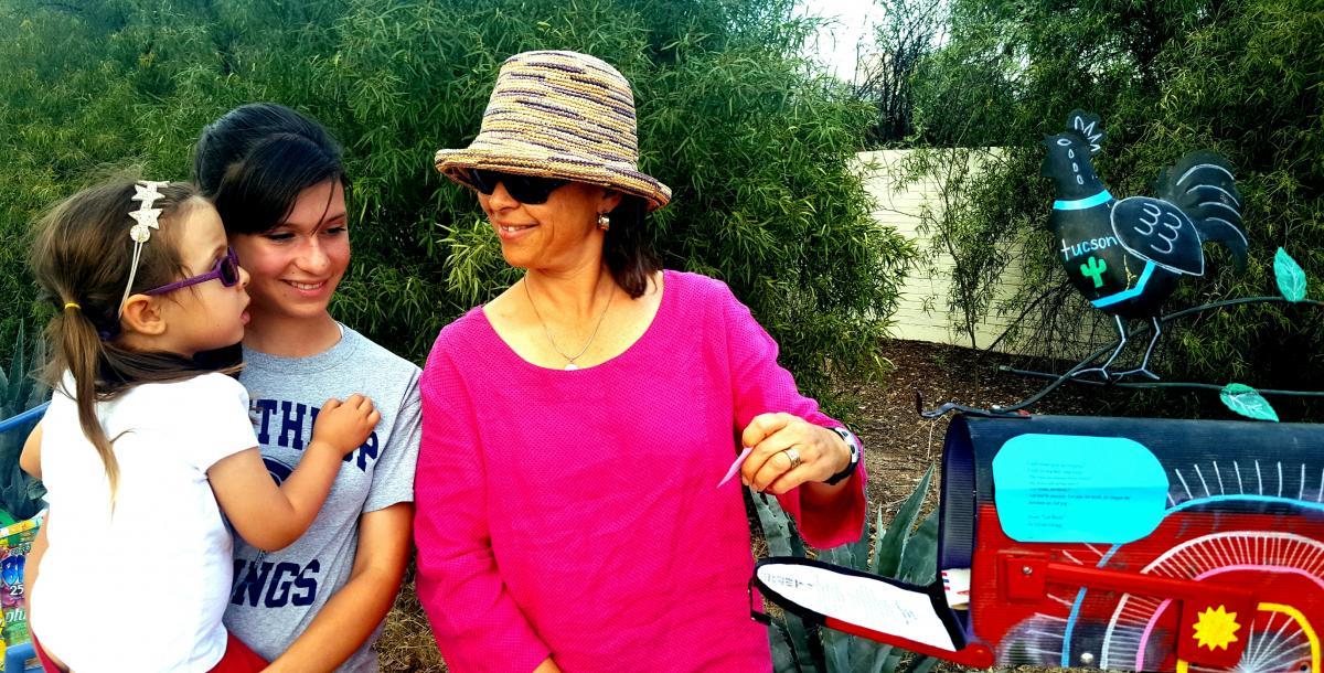 A family visits the Poetry Mailbox to retrieve poems.