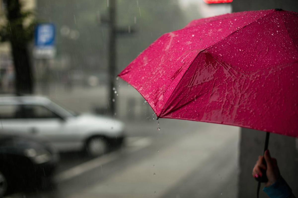 A hand holds a red umbrella on a city street in the rain