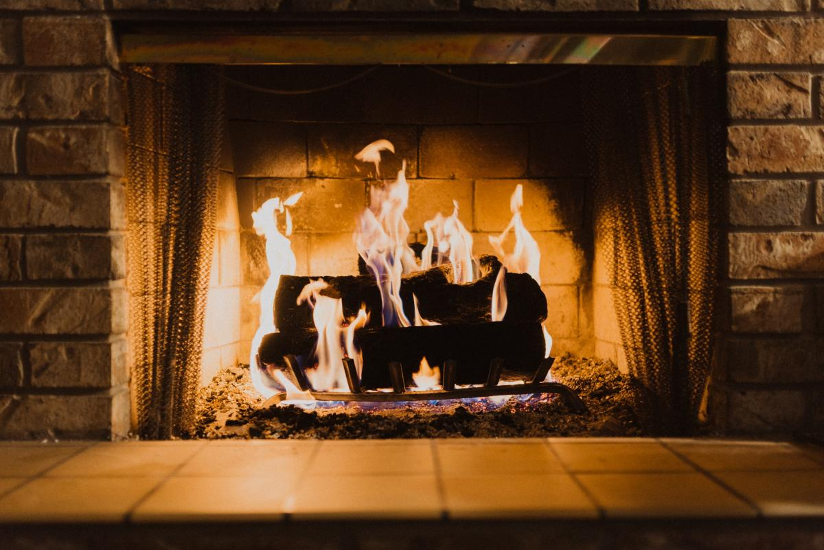 A fireplace with burning logs / photo by Hayden Scott