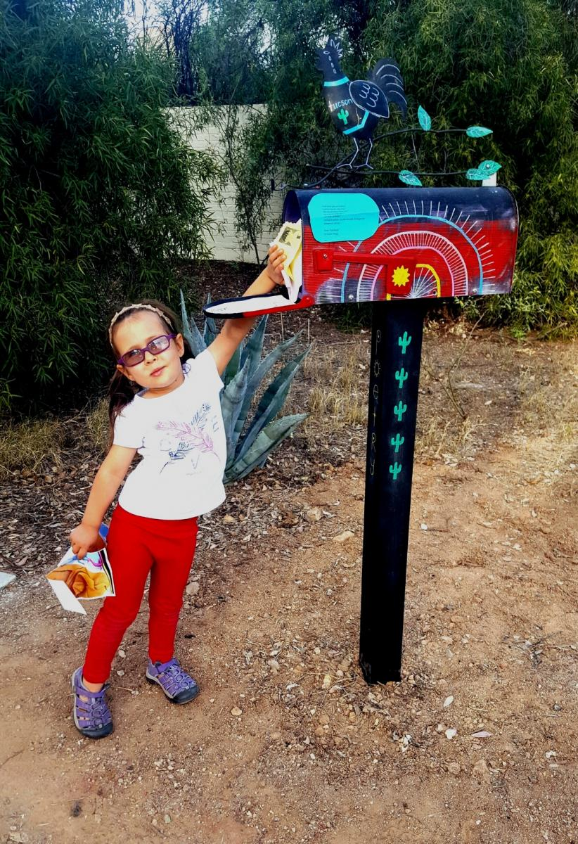 A child reaches up to the Poetry Mailbox to retrieve a poem.