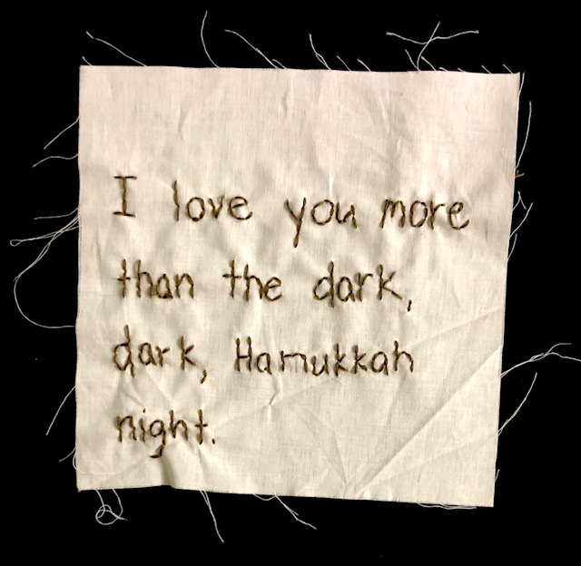 """I love you more than the dark, dark, Hannukkah night"" stitched in brown thread on off-white canvas."