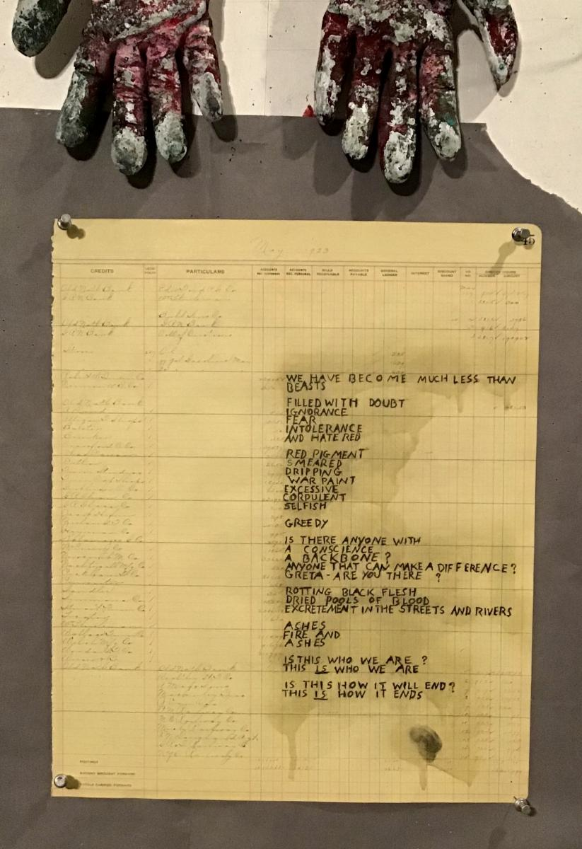 Photo of a poem on ledger paper, with two gloves at the top of the frame.