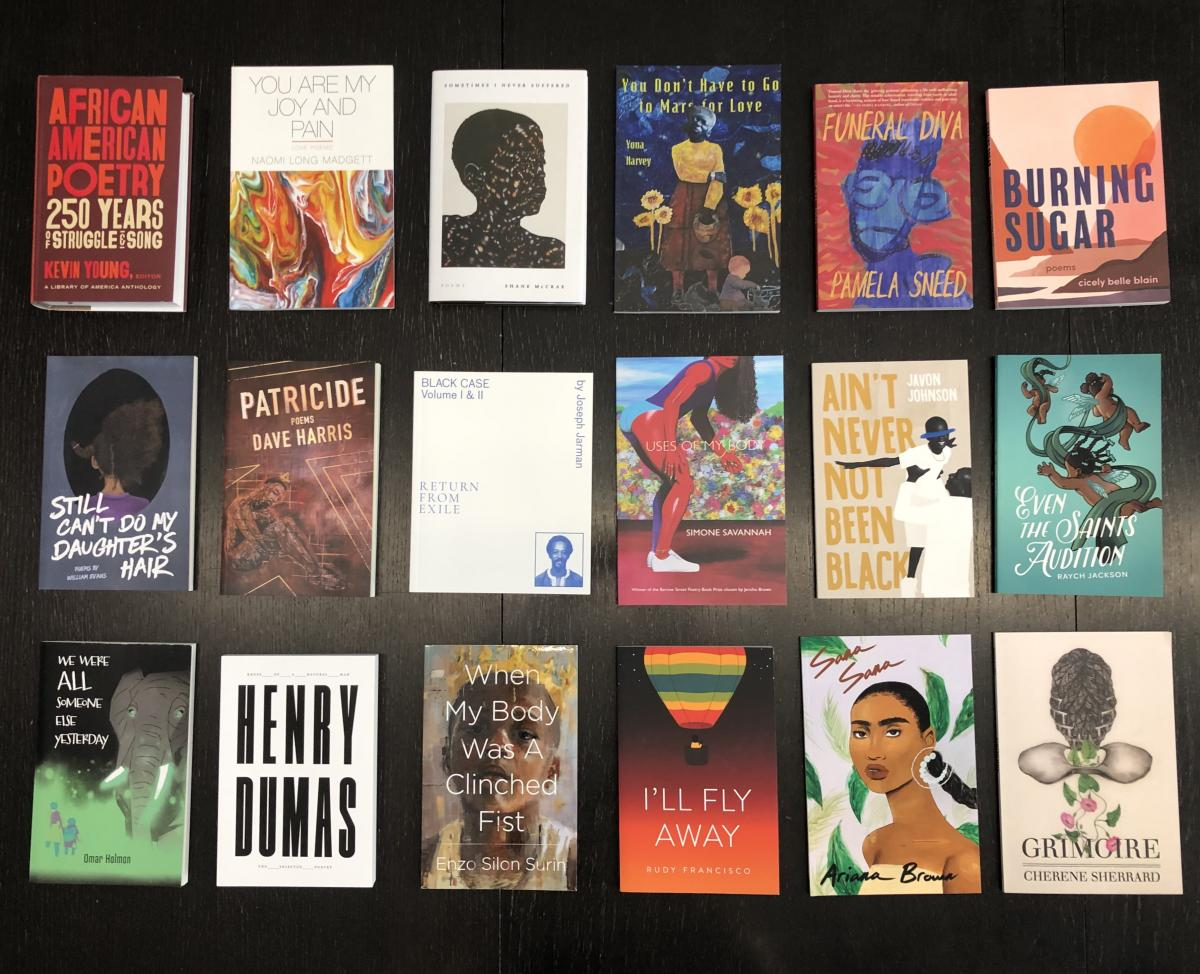 Eighteen books of poetry arranged on a brown wooden table.
