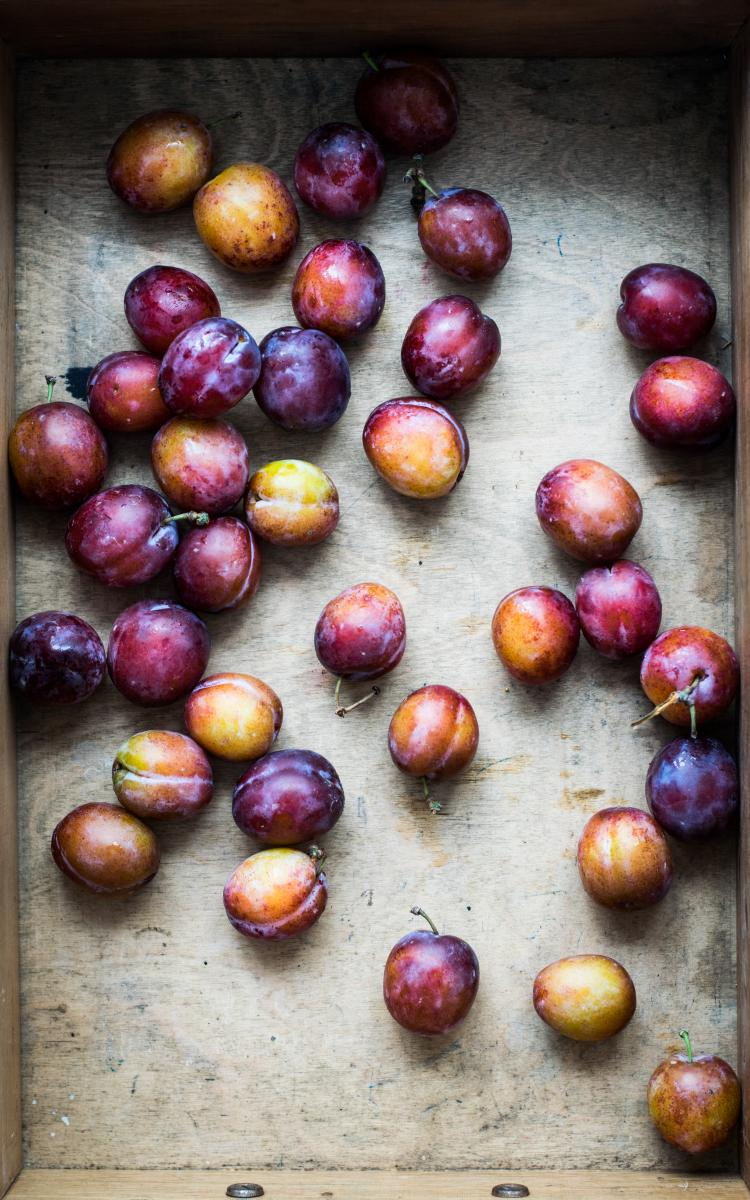 Plums against a wooden background / photos by Monika Grabkowska
