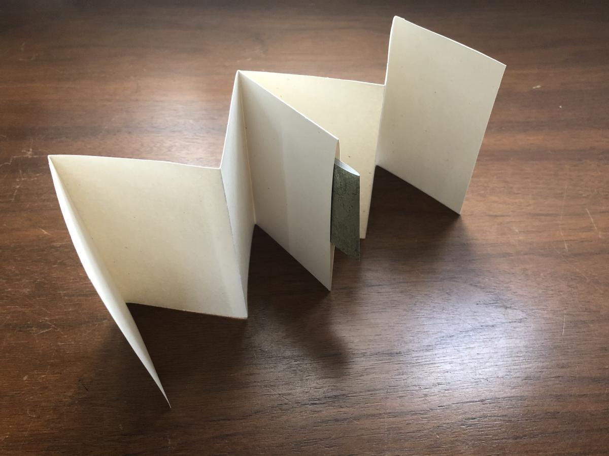 A folded book with a pocket in the middle and a green sheet of paper tucked into the pocket.