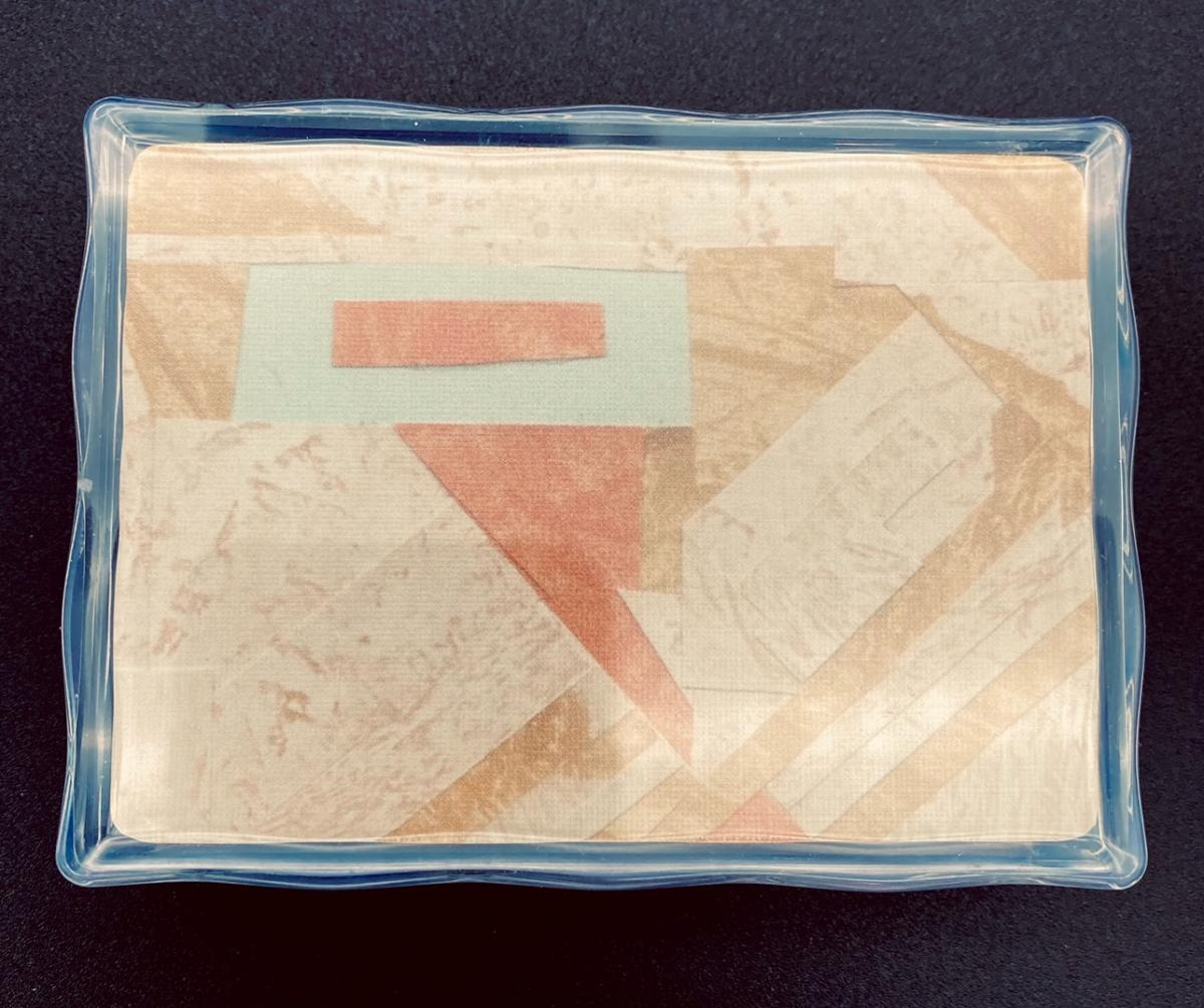 Photo of a clear plastic box containing playing cards made from scraps of wallpaper.