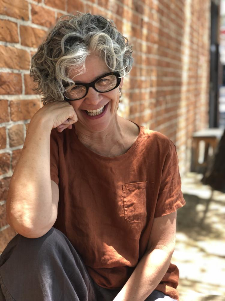 A person with curly gray hair and an ochre tee shirt on sits smiling in front of a brick wall
