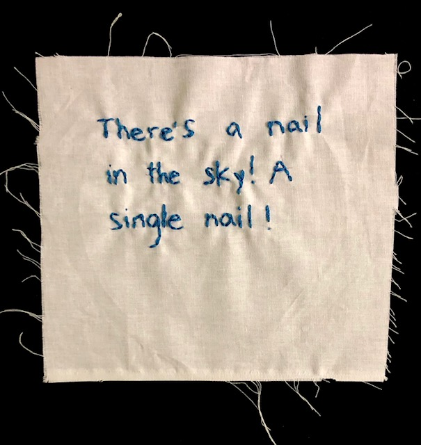 """There's a nail in the sky! A single nail!"" stitched in blue thread on off-white canvas"
