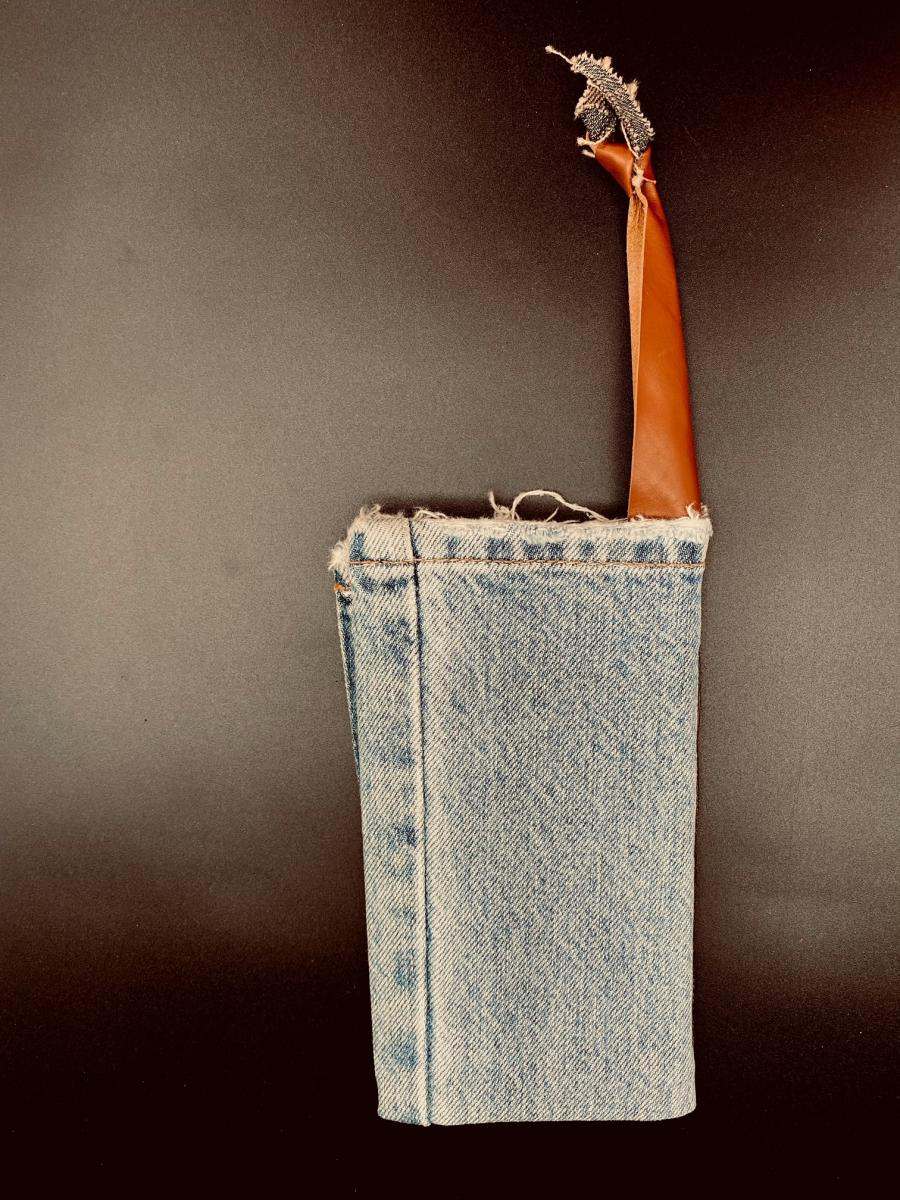 Photo of Totem, a girdle book with a blue-jean cover and leather handle.