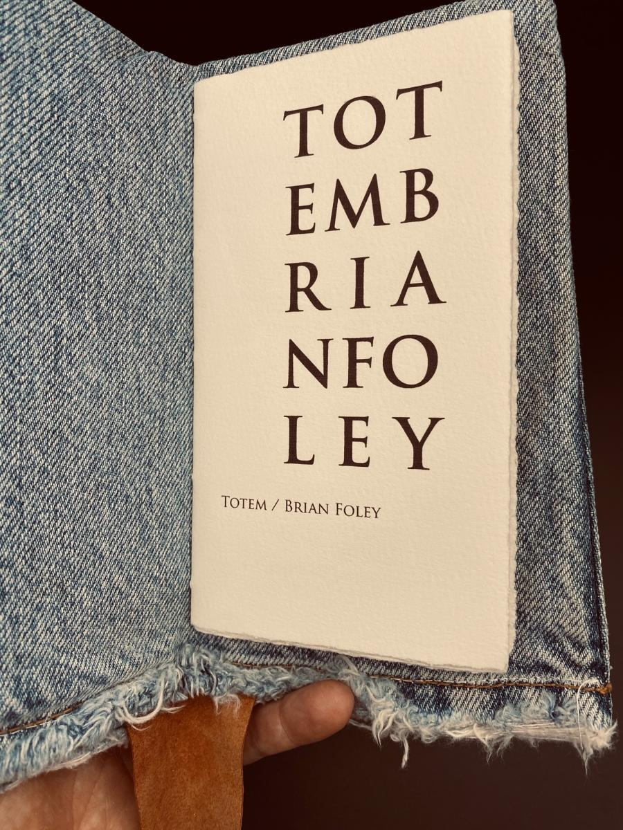 Photo of Totem open to its title page.