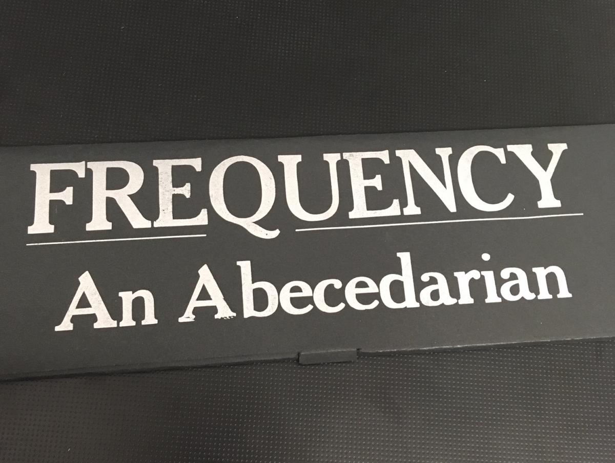 "Photo of ""Frequency: An Abecedarian,"" letterpress silver letters on a black paper box"