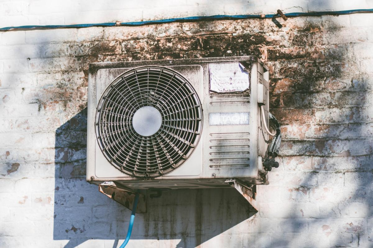 An outside air conditioning unit against a white brick wall