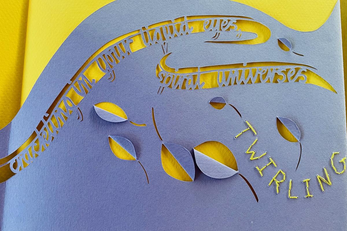 A page from What the South Wind Says, featuring purple and yellow paper and yellow embroidery.
