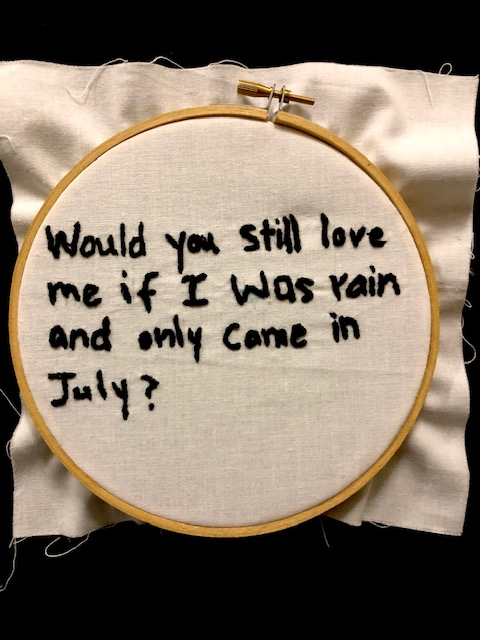 """Would you still love me if I was rain and only came in July?"" in black thread on a white canvas background, set in an embroidery hoop."