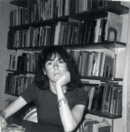 Louise Glück sits at a table with her hand under her chin in front of a bookshelf