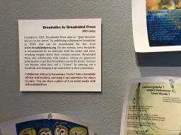A label encouraging people to take home the colorful broadside displayed around the sign on a grey wall.