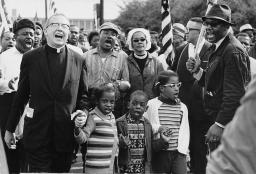 Three small Black children march as part of the Selma to Montgomery March, surrounded by adults