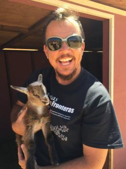 Poet TC Tolbert wears sunglasses and holds a baby goat