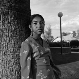 Ai stands in front of a tree in Tucson, in black and white