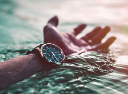 hand in water wearing watch