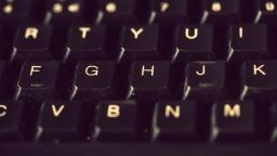 Close-up of black keyboard with a focus on F, G, H, & J keys