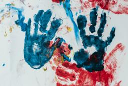Kids handprints in blue and red, photo by Bernard Hermant