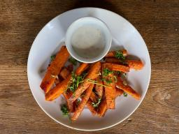 A plate of carrot fries and a small bowl of dipping sauce.