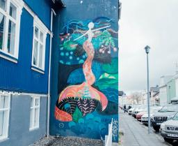 mural of a mermaid on a blue building