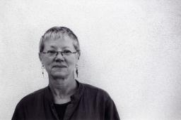 black and white portrait of Linda Gregerson against a white stippled wall