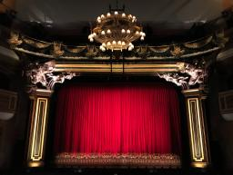 A stage with a red curtain / image by Gwen King