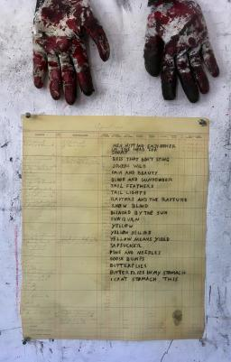 Photo of a poem written on ledger paper, with two work gloves in the top of the frame.