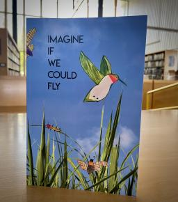"""Book that reads """"Imagine if we could fly"""" with a bird on it, grass, and a blue background"""