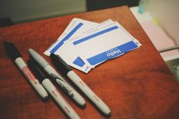 Sharpies sit next to blank name tag stickers on a wooden desk. Photo by Jon Tyson.