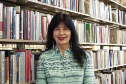 Joy Harjo stands in front of a full bookshelf at the Poetry Center