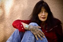 Joy Harjo sits with her knees to her chest and her arm draped over her legs, looking into the camera