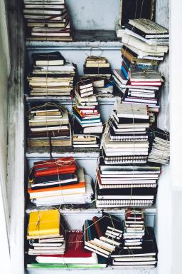 notebooks on an old bookshelf, photo by Julia Joppien