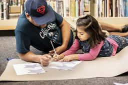An adult and child work on a writing activity together