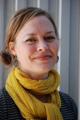 Katherine Larson smiles at the camera, wearing a large yellow scarf