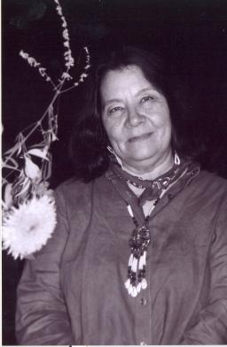 Leslie Marmon Silko stands in the desert at night, a flower near her right shoulder
