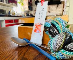 A color photograph of a spoon, a box, a bookmark, and some multicolored yarn.