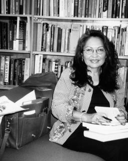 Luci Tapahonso sits in the Poetry Center library, in black and white