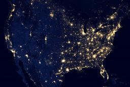 The United States as seen from orbit at night: a dark outline of the continent studded with lights