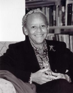 The poet sits in front of a bookshelf in a https://poetry.arizona.edu/sites/poetry.arizona.edu/files/nikki_giovanni_2-26-2006_by_christine_krikliwy.jpgblack blazer
