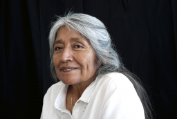 Ofelia Zepeda looks into the camera against a black background
