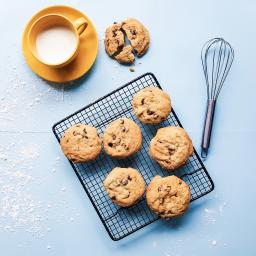 Chocolate chip cookies, milk, and a whisk on a blue table / Photo by Rai Vidanes