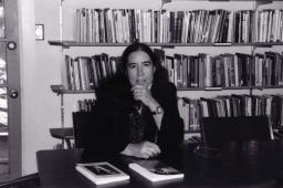Rebecca Sieferle sits at a table with a hand to her chin in front of bookshelves