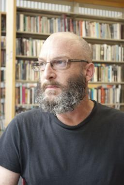 Richard Siken looks into the distance while sitting in the Poetry Center library