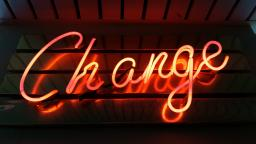 "Neon sign reading ""Change"" in orange text, photo by Ross Findon"